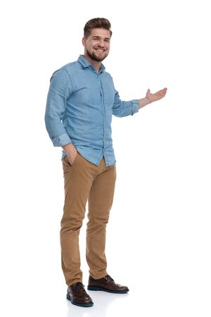 Smiling casual man presenting with his hand in his pocket while standing on white studio background