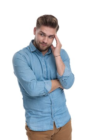 Thoughtful casual man holding his hand on his forehead and looking away while wearing shirt, standing on white studio background