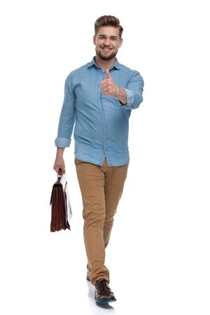 Positive casual man giving thumbs up while holding briefcase and stepping on white studio background