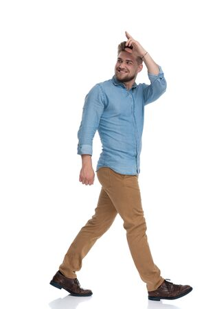 Side view of a positive casual man saluting while stepping on white studio background