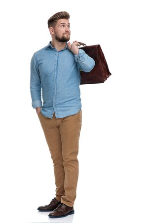 Wondering casual man looking away while holding briefcase and hand in pocket, standing on white studio background