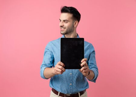 young smiling guy looking to side and presenting tab, standing on pink background Banque d'images