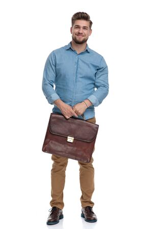 Positive casual man smiling while holding briefcase and standing on white studio background