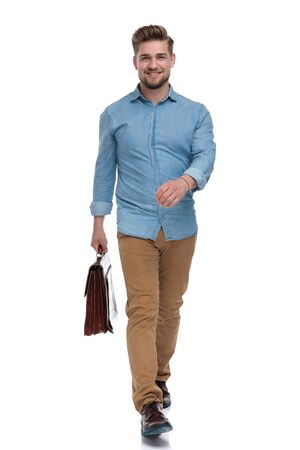 Confident casual man smiling while holding briefcase and stepping on white studio background