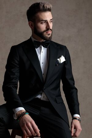Eager groom curiously looking away while wearing tuxedo and sitting on a stool on wallpaper studio background
