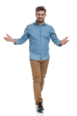 Positive casual man welcoming and smiling while moving on white studio background