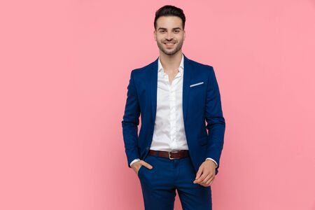 Cheerful businessman holding his hand in his pocket and laughing while wearing blue suit and standing on pink studio background