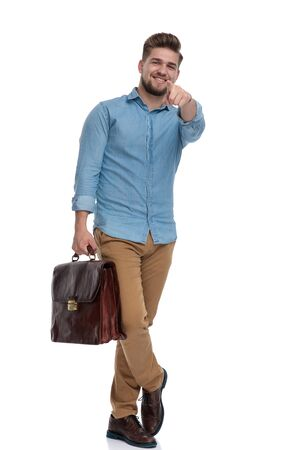 Happy casual man pointing forward, smiling while holding briefcase and standing on white studio background