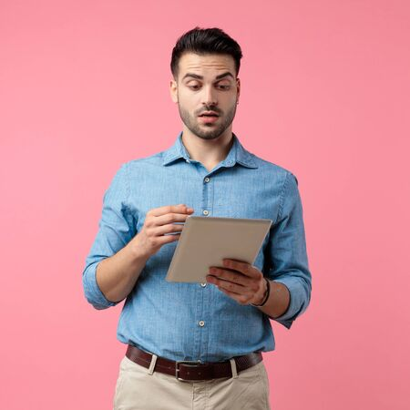 young casual man holding tab and reading news, standing on pink background