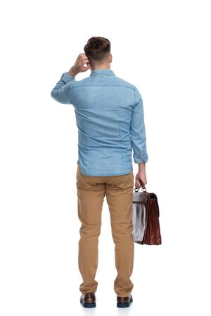 Rear view of a thoughtful casual man scratching his ear and holding briefcase, standing on white studio background