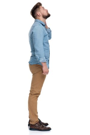 Side view of a motivated casual man looking up, standing on white studio background Reklamní fotografie