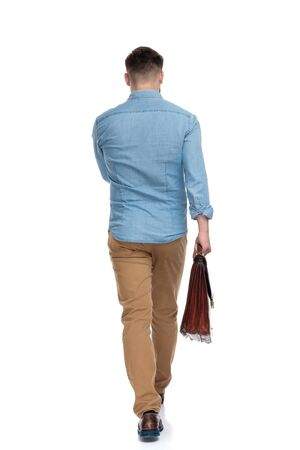 Rear view of a determined casual man holding briefcase and walking on white studio background