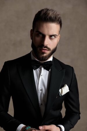 Bored groom rolling his eyes and making funny face while wearing tuxedo and sitting on a stool on wallpaper studio background