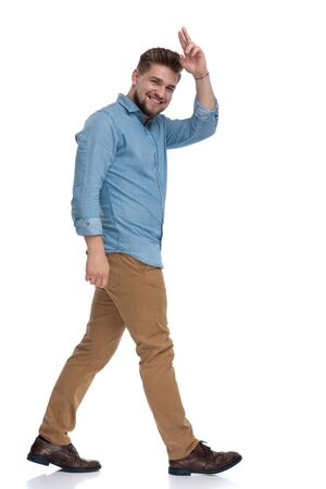 Side view of a happy casual man greeting and laughing while stepping on white studio background