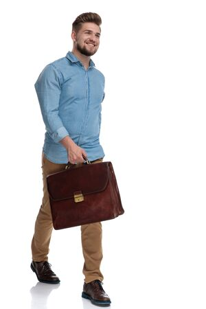 Cheerful casual man laughing while holding briefcase and stepping on white studio background Reklamní fotografie