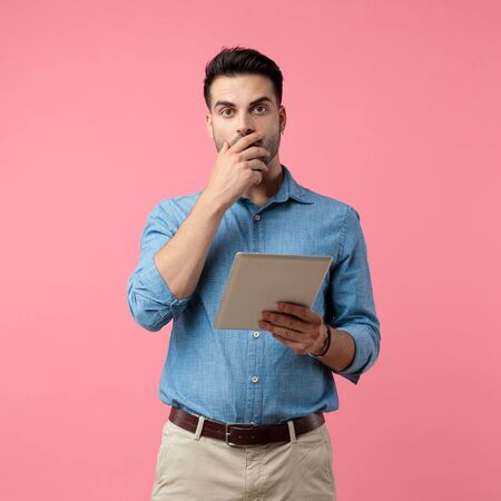 shocked casual guy holding tab and covering mouth with hand, standing on pink background