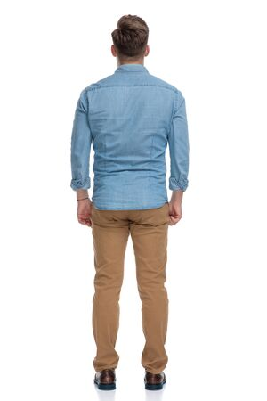Rear view of a confident casual man standing on white studio background Reklamní fotografie
