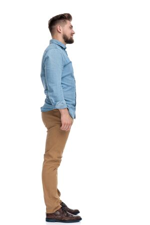 Side view of a confident casual man looking forward, standing on white studio background