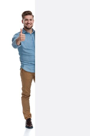 Positive casual man giving a thumbs up and smiling behind a blank billboard while standing on white studio background