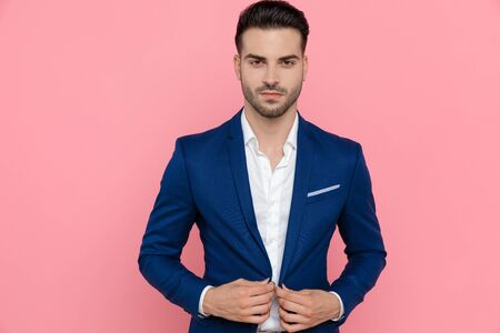 Confident businessman adjusting his jacket while wearing blue suit and standing on pink studio background