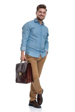 Handsome casual laughing while holding briefcase and hand in pocket, standing on white studio background