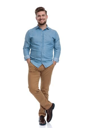 Happy casual man holding both hands in his pockets and smiling while standing on white studio background