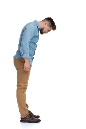 Side view of a eager casual man curiously looking down, standing on white studio background