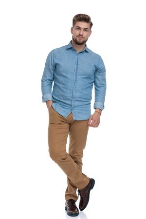 Charming casual man posing with his hand in his pocket while standing on white studio background