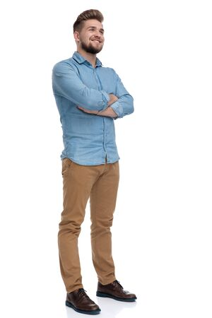 Hopeful casual man looking away with his hands crossed at his chest while standing on white studio background