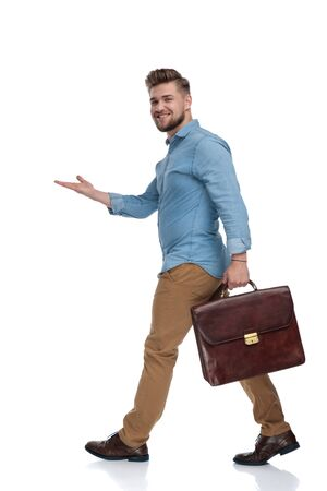 Side view of a happy casual man presenting while holding briefcase and walking on white studio background