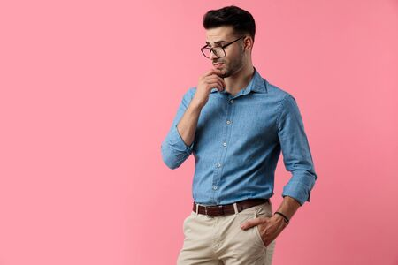 suspicious young guy wearing glasses and looking to side, holding hand to chin and wondering, standing on pink background