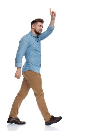 Side view of a cheerful casual man greeting while walking on white studio background