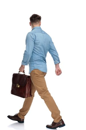 Side view of a determined casual man holding briefcase and walking on white studio background Reklamní fotografie
