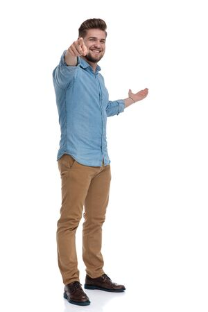 Happy casual man pointing, presenting and smiling while standing on white studio background