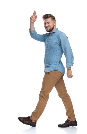 Side view of a cheerful casual man greeting and laughing while stepping on white studio background Reklamní fotografie