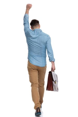 Rear view of a celebrating casual man holding briefcase and standing on white studio background