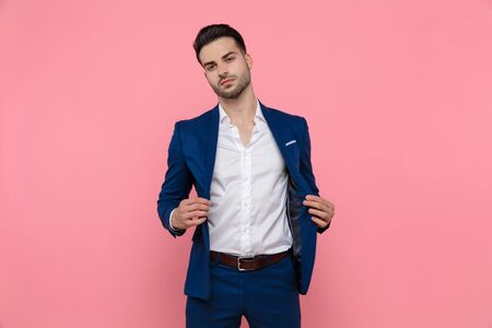 Charming businessman taking off his jacket while wearing blue suit and standing on pink studio background