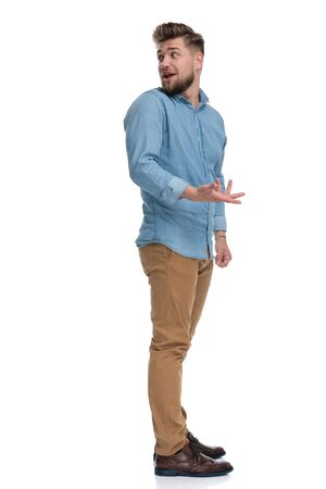 Side view of a casual man explaining and gesturing, standing on white studio background