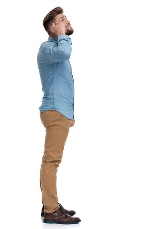 Side view of a casual man pointing to his head and looking up, standing on white studio background