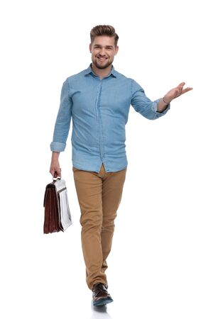 Smiling casual man presenting while holding briefcase and stepping on white studio background