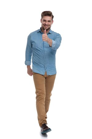 Cheerful casual man smiling and giving a thumbs up while moving on white studio background