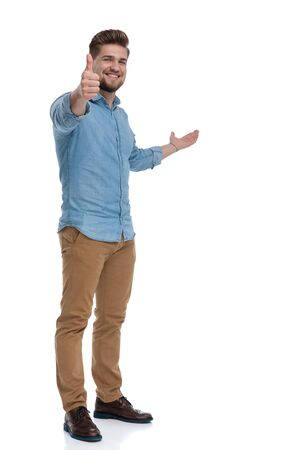Positive casual man gesturing ok, presenting and smiling while standing on white studio background Reklamní fotografie