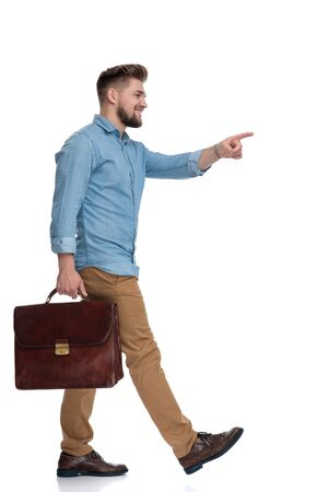Side view of a cheerful casual man pointing while holding briefcase and stepping on white studio background Reklamní fotografie