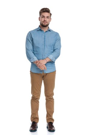 Focused casual man looking forward and listening while standing on white studio background
