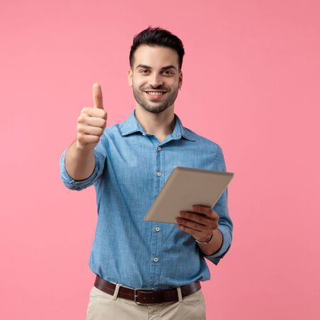 young casual guy making thumbs up sign and holding tab, standing on pink background