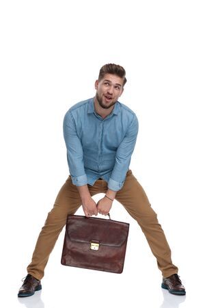 Young casual man making a funny pose while holding briefcase and standing on white studio background
