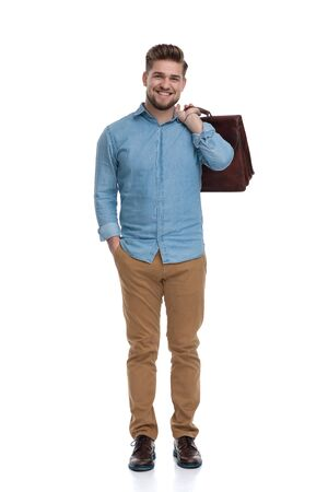 Happy casual man laughing while holding briefcase and hand in pocket, standing on white studio background Reklamní fotografie