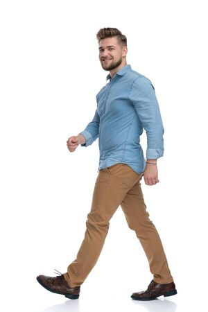 Side view of a confident casual man walking on white studio background