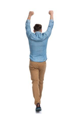 Rear view of a celebrating casual man walking on white studio background Reklamní fotografie