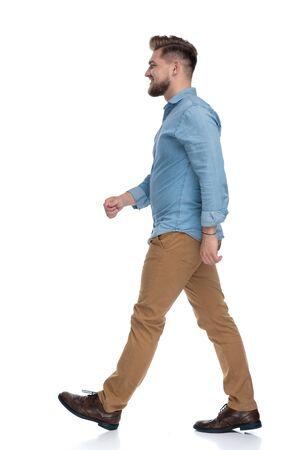 Side view of a happy casual man walking on white studio background Reklamní fotografie